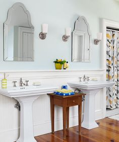 Curvaceous mirrors, a freestanding table, and new pine flooring reinforce the mix of period style and contemporary function in this master bath. | Photo: Tria Giovan | thisoldhouse.com