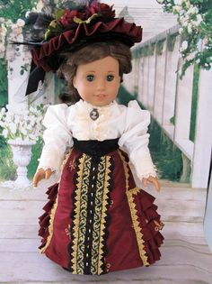 Deep rich colors, elegant gold trim and a stylish pleated train make this a must for any young lady of the Victorian era! The fully lined jacket is made of a soft burgundy fabric with accents of metallic gold lace, black applique and antique gold metal closure. The skirt made of