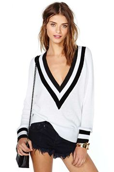 This prep school sweater features a deep V-neck with black and white ribbed detailing.