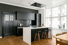 Mustavalkoinen keittiö on remontoitu muutama vuosi sitten sekoittaen modernia ja vanhan talon henkeä. Upea avokeittiö kätkee minimalistisen tyylikkäästi sisälleen kaiken tarpeellisen ja ikkunoista avautuu hienot näkymät merelle.