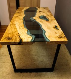 River table made of old solid timber. Filled with blue epoxy resin and blue transparent glass. Legs made of metal coated with mat black colour.