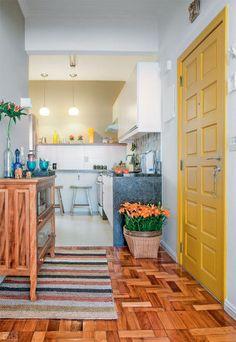 Para a conquista de um hall maior, a cozinha perdeu uma de suas paredes, abrindo-se para a ala social. Apenas o piso de porcelanato marca o limite do ambiente – do outro lado, foi mantido o taco original de madeira. Projeto de Marcel Rofatto e Eliete Mourão.