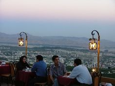 Youngsters sitting on the patio of a restaurant up on the mountain slopes surrounding Tehran with panoramic views of the capital.
