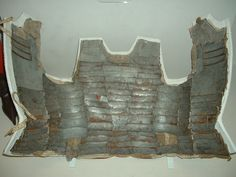 """Brigandine, Italian, c1470, Royal Armoury, Leeds """"Shown opened out to reveal its construction. Its name was derived from the infantry 'brigans' who first wore it. It was formed of tinned iron plates riveted inside a canvas jacket. This example is covered with dark brown or black fustian (soft cotton cloth)."""" [Source: Wikipedia]"""