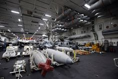The aircraft and ordnance in a hangar aboard the giant aircraft carrier USS Theodore Roose...