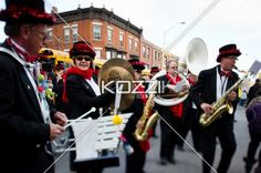view of a musical band with musical instruments. - View of a musical band performing on road at Christmas parade.