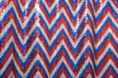 The bright colors of the Good ol' USA and one of the most popular décor patterns in the last decade all in one great eye popping fabric! Order soon for delivery by the Memorial Holiday and bring it back out for those Fourth of July celebrations! Red, royal blue and silver holographic sequins in a chevron design paired with premium white poly/cotton polished fabric for our Hostess Aprons and our signature Poly Burlap in bright white for our table linens!