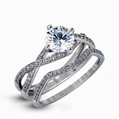 This sparkling modern white gold engagement ring and wedding band set features an eye-catching twisted design accented by .22 ctw of shimmering round cut white diamonds.