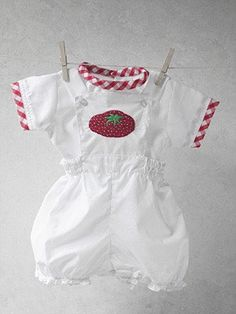 Big Tomato Dungarees Set  A huge, juicy, hand-embroidered tomato adorns the bib of these dungarees. The set features a rear-fastened top with matching, red trim around the neck and sleeves. This vibrant and attractive set can be enjoyed for even longer as we fully elasticate the waist and legs, and include an extra button on the straps to accommodate your growing baby.