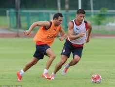 Cazorla (left) and Giroud go for the ball at theArsenal training session before their fri...