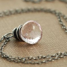 This necklace features a plump, sparkling pink quartz briolette wrapped in sterling silver wire.