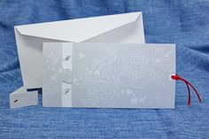 Partecipazione con copertina a tasca cuori e rose in rilievo e bianco a caldo, fustellata in modo da vedere le iniziali degli sposi.  All'interno un intercalare in cartoncino goffrato di colore bianco.  A rifinire l'intercalare, un nastro di doppio raso di colore rosso.  Partecipazione con spazio previsto per l'invito pranzo/cena o al taglio della torta/party.  Formato 21 x 10,5 cm.  ARTICOLO MADE IN ITALY