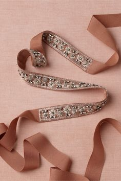 Galaxie Sash    Silvered beading and metallic embroidery orbit a slim grosgrain ribbon, for a versatile adornment that feels both vintage and very modern. Designed by Hitherto, exclusively for BHLDN. Self-tie. Rayon, metallic cotton, glass beads and crystals. Imported.