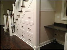Custom built-in drawers/desk under the stairs.