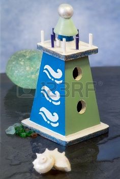 decorative wooden lighthouse with seashell over ardesia Stock Photo