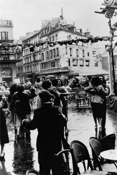 Couples dancing despite the rain in the squares for the July 14th, 1951 national holiday in Paris, France.
