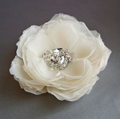 These flowers start out as light ivory silk chiffon fabric that is hand cut and pressed into petals to form the flower.This is a smaller flower than the other Hera flower.The centers are beaded with genuine crystal quartz, freshwater pearls and white topaz gemstones along with rhinestones to finish off the sparkle.*****Please allow two weeks to ship*****Perfectly soft in every way.Flower measures about 3 inches in diameter or about 7-8 cm. Available as a flower hair clip or a brooch…