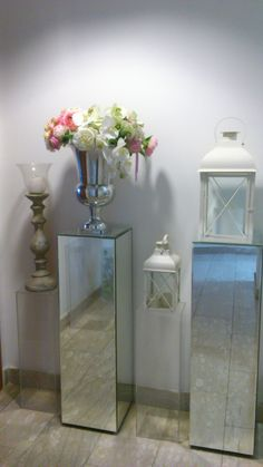 tall mirrored pillars with lanterns and vases