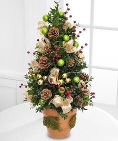 Festive traditions abound with this merry boxwood tree laced with all the holiday trimmings. Send this gift and share the magic of the season.