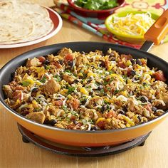 Chicken, black beans, zesty tomatoes and taco seasoning cooked together with brown rice for an easy burrito skillet topped with cheese