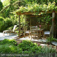 Natürlicher Garten mit überdachter Sitzecke.  Ähnlich wie ein Carport sieht das umrankte Dackwerk aus. Schön! Outdoor-Sommer-Feeling!