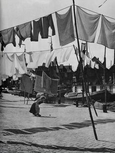 ed van Wijk,Spakenburg,j 50 | Flickr - Photo Sharing! Baby girl or boy playing with a top under the laundry line.