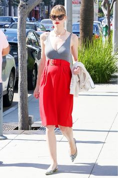 Jaime King wears a gray bodysuit tucked into a red high-waisted skirt with printed sling-back flats