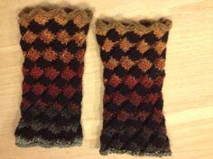 Skrå rib i 2 farver - strikkes rundt:  Maskeantallet skal være deleligt med 6  Slå masker op med farve A på 4 strømpepinde eller med magic loop metoden.  P1: * 2r, slå o, 2r, strik 2 m sm, gentag fra * omgangen rundt  Strik yderligere 3 omg.  Skift til farve B og strik 4 omg.  Disse 8 omg gentages, til du har den ønskede længde.  Det er bedst at strikke i fyldigt garn på lidt tyndere pinde end du ellers ville bruge til garnet.  Jeg har slået 48 m op på p 3.