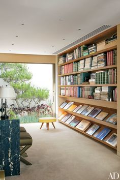 A vintage William Haines stool sits in the library, next to walnut bookshelves | http://archdigest.com
