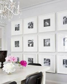White framed, white backing, black and white photographs.  Six frames on one wall and 4 frames on the smaller wall.
