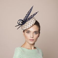 Gina Foster Millinery - Capri - Feather Cocktail Hat The Capri is a natural pinok pok base with navy overlay, chequered feather and pinok pok ribbon trim. Simple yet sophisticated, can be worn for any occasion. Secured with an elastic that sits on the right side of the head.