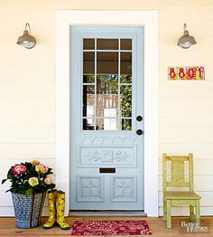 New glass, paint, and hardware improve the decorative front door, which was purchased secondhand for just $100. An olive bucket makes a rustic container for colorful blooms, while handpainted address tiles demonstrate an easy and inexpensive DIY project with personality.