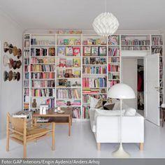 Fußboden, Sofa, Lampen, Bücherregal und Wandfarbe - alles ist Weiß. Und dennoch wirkt die Wohnzimmereinrichtung nicht kalt, da Holzmöbel und Accessoires wie…