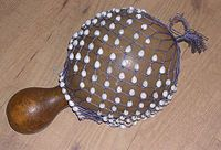 The shekere is an instrument from West Africa consisting of a dried gourd with beads woven into a net covering the gourd. In Brazil, this African gourd rattle is called a xequerê. It consists of the gourd (cabaça) cut in the middle and then wrapped in a net in which beads or small plastic balls are threaded.