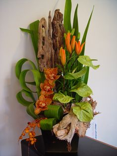 Orange orchids, lime antheriums and driftwood.