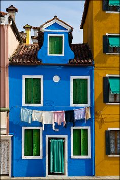 I pinned this for the windows. the green shutters and the awnings. I love the curtain door and the yellow for the building oh and the clay tile roof. Colourful Buildings, Beautiful Buildings, Beautiful Places, Colorful Houses, Blue Shutters, Ivy House, Windows And Doors, House Colors, Bunt