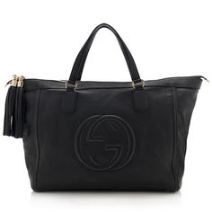 This iconic Gucci tote is made from pebbled black leather with a central interlocking-G logo and pale gold-tone hardware. Details include two flat handles, a double-zip closure, and fully lined interior with two open pockets and one zippered pocket.