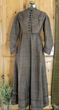 "1840s-60s wool challis, light gray, brown  white, hand sewn, 9 fabric covered buttons, two hooks across waist, top is like a corset with 2 small holes on each side under the breast, light cream lining on bodice & hem, pleated skirt; length: 50.5""; waist: 29"""