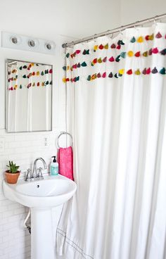 A Beautiful Mess bathroom makeover: tassel shower curtain. Love the all white and pop of color for kids' bathroom