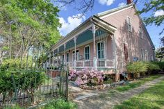 """Called """"Pink Moon Guest House,"""" this lovely four-bedroom, four-bath home dates back to the late 1800s. It has all the hallmarks of a great Victorian: charming details, a colorful exterior and a relaxing porch."""