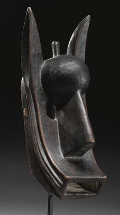 A BAMANA MASK, MALI, of hollowed form, carved with the abstract features of a hyena with squared mouth, massive flat nose, bulging forehead, two elegantly curved ears and a cylindrical protrusion in between; varied brown patina.  height 19 in. 48.2 cm