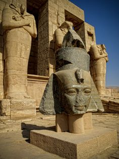 Ramesseum | Granite head of Ramesses II (1279-1213 BC, 19th Dynasty) at his memorial temple. In the background are three Osiride pillars (engaged statues which depict the Pharaoh in the form of the god Osiris).