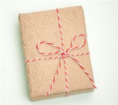 Simple holiday gift wrap: textured craft paper with red and white twine