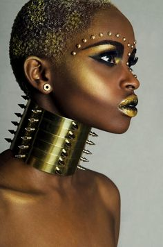 Woman wearing a gold neck choker & gold makeup