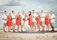Outstanding coral short dresses and beachy khaki shorts and white shirts groomsmen attire for a unique tropical paradise wedding at Key Largo Lighthouse Beach Wedding Venue in the Florida Keys