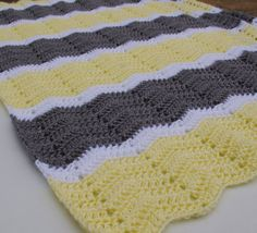 A crochet baby blanket is a perfect shower gift for mom-to-be. This crochet baby afghan is handmade in a ripple, chevron pattern in soft, machine washable acrylic yarn. The colors are pale yellow, grey and white. Generously sized at 29 x 45 (74cm x 114cm) this afghan will grow with baby into the toddler years. Its perfect for the crib, the car, the stroller or for tummy time on the floor. All of my items are hand crocheted in a smoke-free, pet-free home.