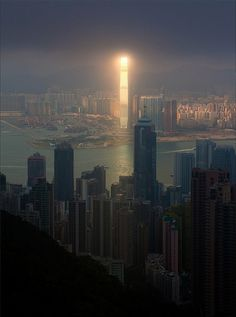 A bright beam of sunlight illuminates one of the tallest buildings in the world - the 1,588ft tall, 108-floor International Commerce Centre in Hong Kong - while leaving the rest of the cityscape in cloudy darkness. By photographer Pavel Kiselev.