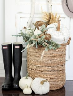 Plush pumpkins amidst autumnal greenery make a subtle and elegant statement on this pretty front porch, and can be left up far after Halloween is over. | Source: Craftberry Bush