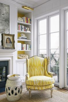yellow upholstered chair, garden stool, white bookcases, yellow wallpaper, styled bookcase, antique mirror, art lamp