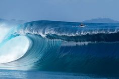 Picture of surfer Sean Woolnough paddling at the top of a wave, Fiji